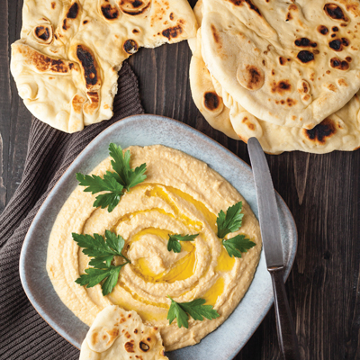Plate of hummus with flat breads on wooden table, close up