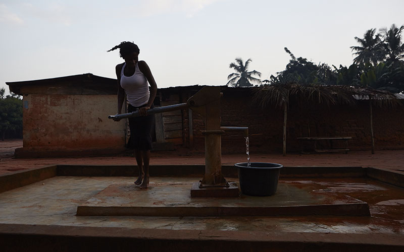 Une mère de 5 enfants d'Akwateakwaso, au Ghana, en train de puiser l'eau nécessaire à la culture des céréales. (Photo: Acqua For Life)