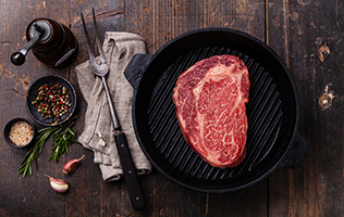 Raw fresh Black Angus Steak on grill pan on wooden background