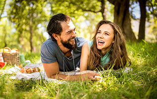 Girl laughing happily with her boyfriend relaxing on a blanket in the grass at a picnic in a sunny park