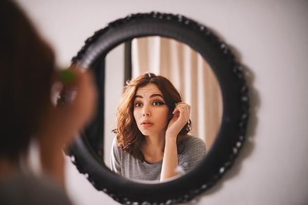 Jeune femme qui se maquille devant le miroir