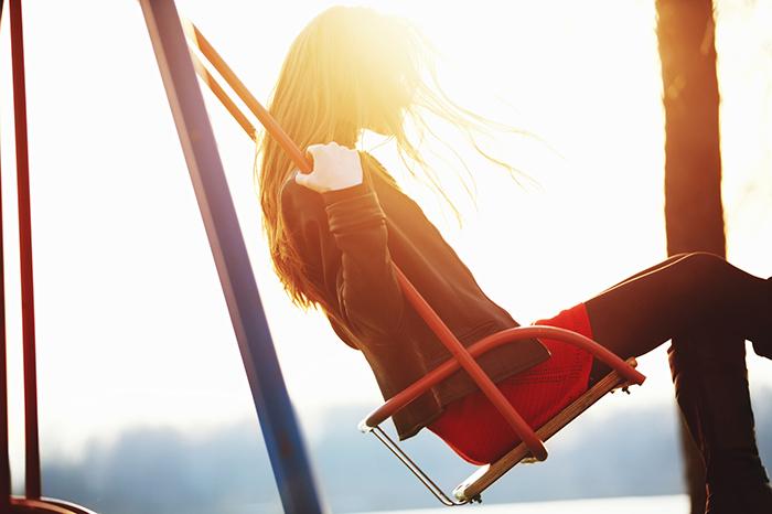 Young woman enjoying swinging in sunlight