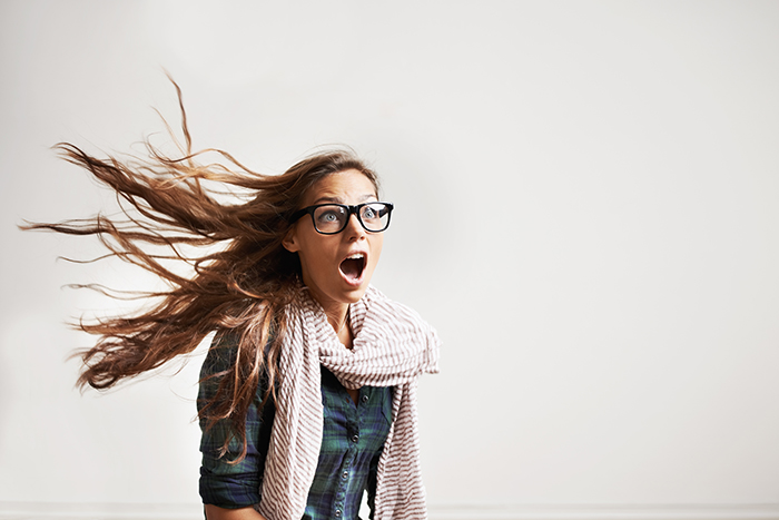 A shocked trendy girl with wind blowing her hair back alongside copyspace