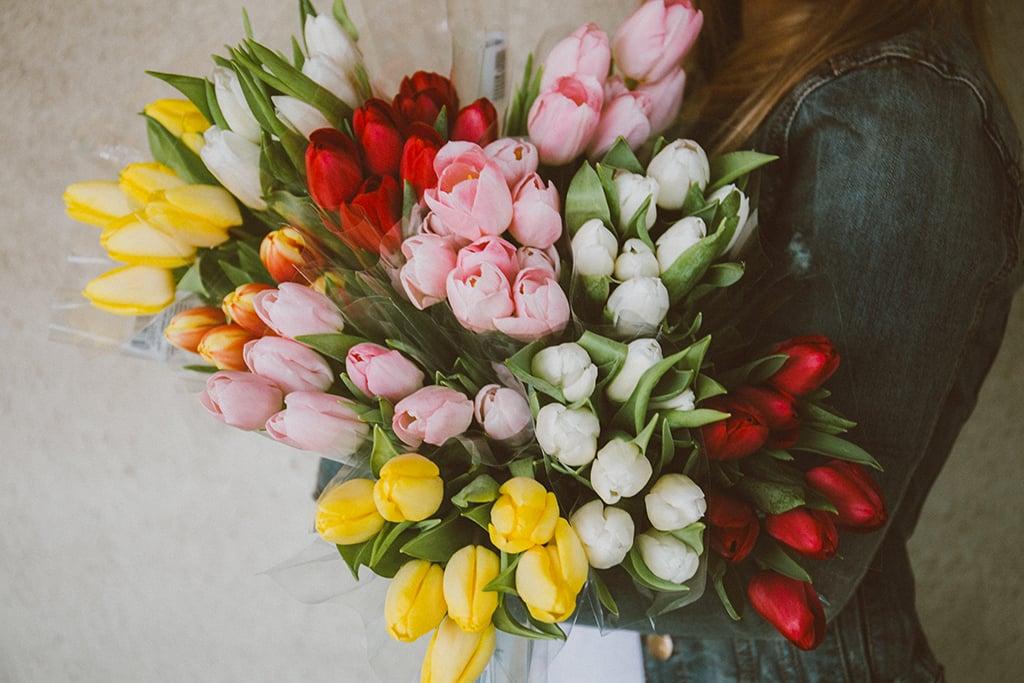 Femme qui a dans ses bras un bouquet de tulipes.